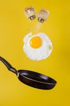 Breakfast time. a fried egg and a frying pan with salt shakers levitate in the air