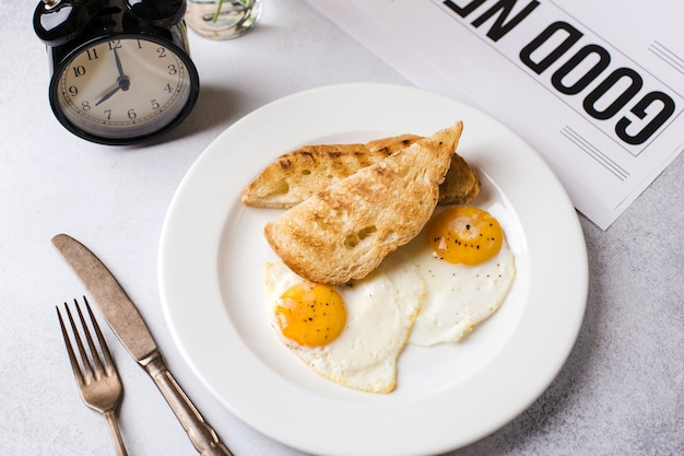 Breakfast time. two fried eggs with toast for breakfast on a textured light gray background with a newspaper and an alarm clock