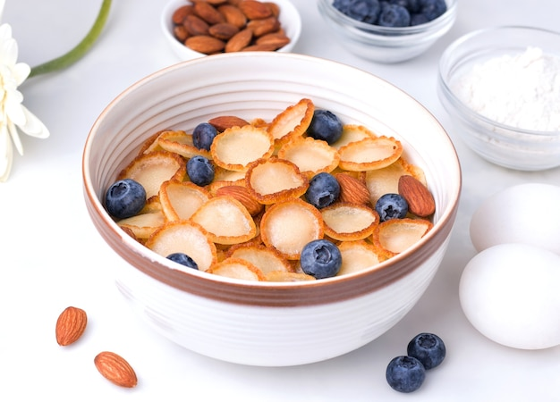 Breakfast of tiny pancake cereal with blueberries and almonds on a white plate next to the ingredients