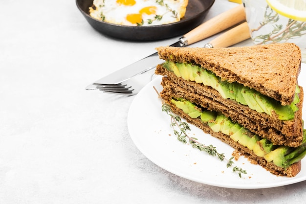 Breakfast - a toast from rye bread with avocado, fried eggs