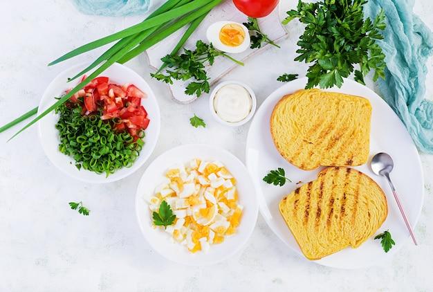 Тост на завтрак. здоровый бутерброд с салатом из помидоров и яиц с сыром на завтрак. вид сверху, сверху, плоская планировка