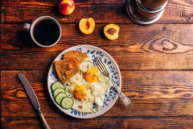 접시에 야채와 함께 튀긴 계란을 곁들인 아침 토스트와 어두운 나무 배경 위에 과일을 곁들인 커피 한 잔, 위쪽 전망. 깨끗한 식사 개념입니다.