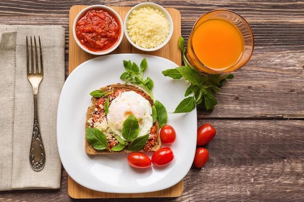 소박한 나무 표면에 데친 달걀, 토마토 소스, 바질, 파마산 치즈를 곁들인 조식 토스트