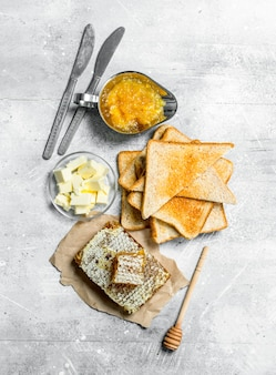 Breakfast. toasted bread, honey with orange jam and butter. on a rustic surface.