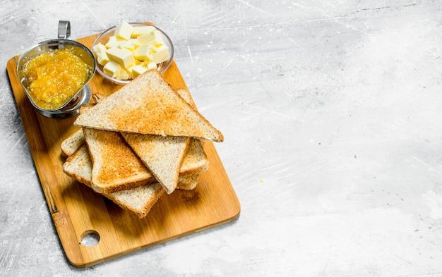 朝ごはん。木の板にバターとジャムを添えたトーストしたパン。素朴なテーブルの上。