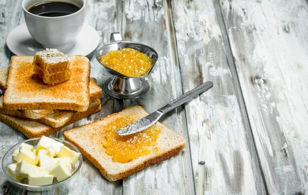 朝ごはん。オレンジジャムのトーストパン。木製の素朴なテーブルの上。