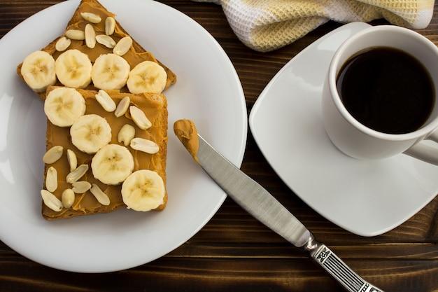 朝食:茶色の木製の背景にピーナッツペースト、バナナ、コーヒーとトースト。上からの眺め。