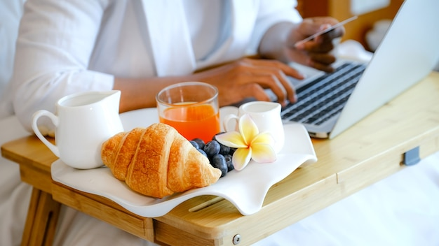 Breakfast in a tray on the bed in the luxury hotel room in front of an asian businesswoman traveler using a laptop.