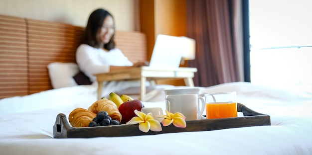 Breakfast in a tray on the bed in the luxury hotel room in front of an asian woman traveler using a laptop.