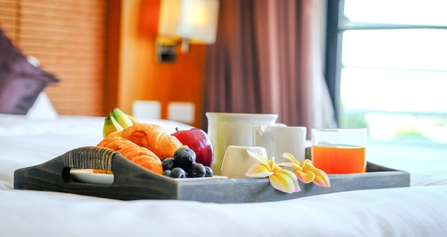 Breakfast in a tray on the bed in the luxury hotel room ready for tourist travel.