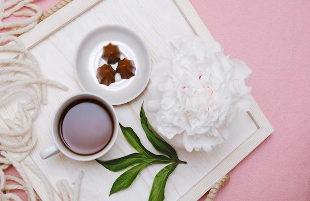 ベッドの朝食トレイ:コーヒー、キャンディー、花。