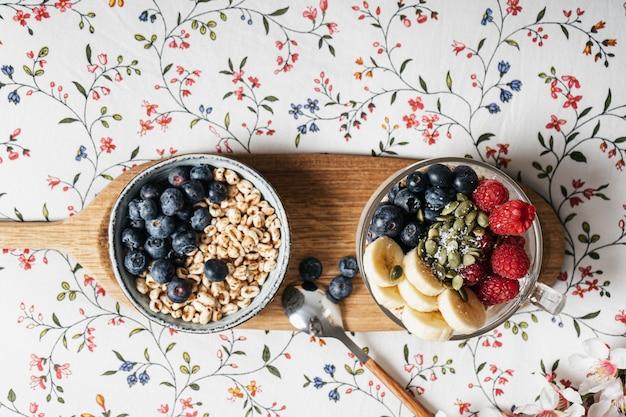 シリアル、ヨーグルト、フルーツをベッドに置いた朝食トレイ