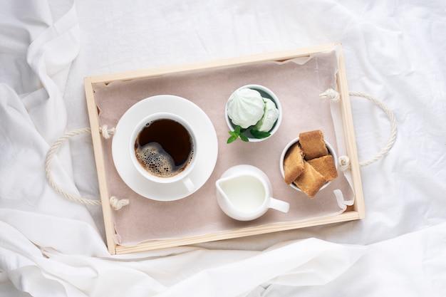 Поднос завтрака, утренний кофе с конфетами на белой кровати, вид сверху.