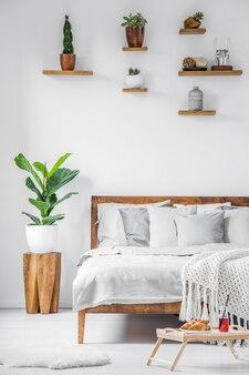 白い寝室のインテリアにリネン、毛布、枕が付いた大きな快適なベッドの横の床に立っている朝食トレイ。本物の写真。