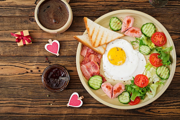 Breakfast on valentine's day - fried egg in the shape of a heart, toasts, sausage, bacon and fresh vegetables. english breakfast. cup of coffee. top view