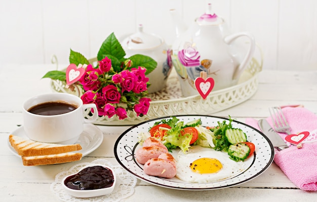 Breakfast on valentine's day - fried egg in the shape of a heart, toasts, sausage and fresh vegetables. cup of coffee. english breakfast