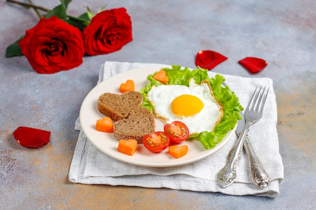 Breakfast on valentine's day - fried eggs and bread in the shape of a heart and fresh vegetables.