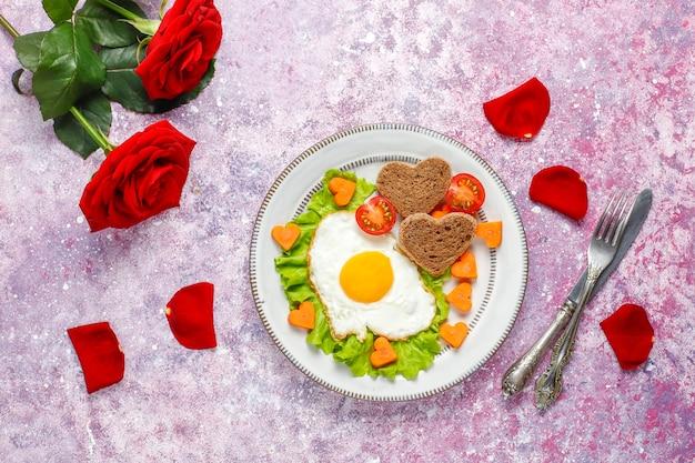Colazione di san valentino: uova fritte e pane a forma di cuore e verdure fresche.
