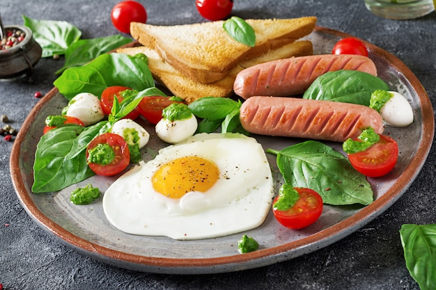 Breakfast on valentine's day - fried eggs in the shape heart, sausage, toast and caprese salad