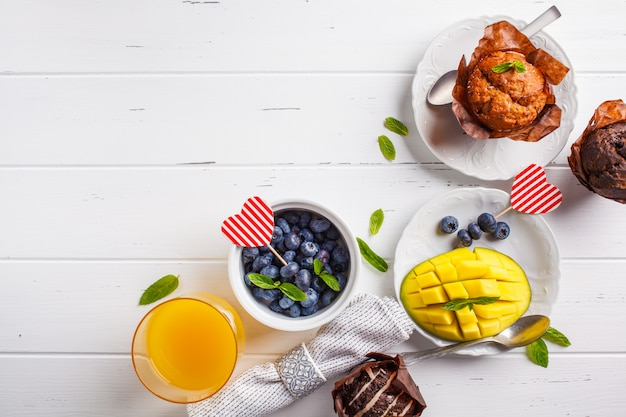 Breakfast on valentine's day served with muffins, juice, berries and fruit, top view, white background.