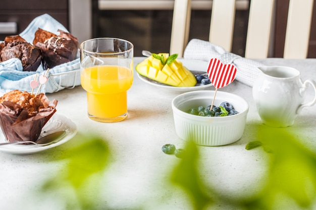 Breakfast on valentine's day served with muffins, juice, berries and fruit.