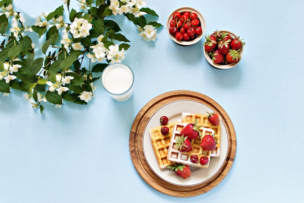 Breakfast. viennese waffles with strawberries and cherries on a wooden board. spring