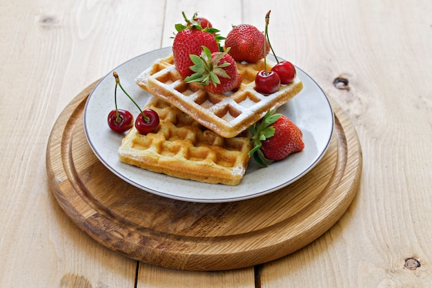 Breakfast. viennese waffles with strawberries and cherries on a wooden board. spring.