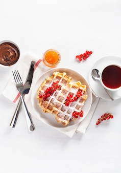 Breakfast waffle with berry, jam, chocolate spread and tea. top view