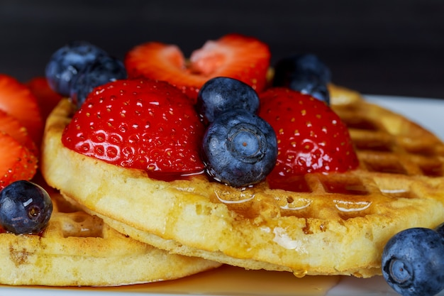 Breakfast waffle with fresh blueberries, strawberries and maple syrup