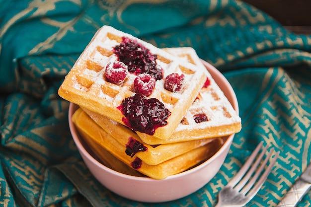Вафли завтрака со свежими ягодами укладываются в миску.