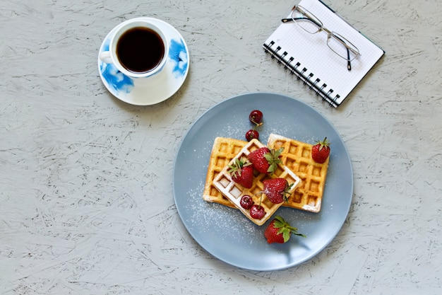 Breakfast. waffles with strawberries and cherries. notebook, pen, glasses, coffee.