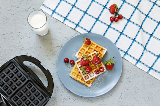 Breakfast. waffles with strawberries and cherries. notebook, pen, glasses, milk. waffle iron