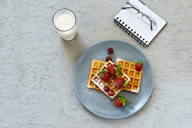 Breakfast. waffles with strawberries and cherries. notebook, pen, glasses, milk.