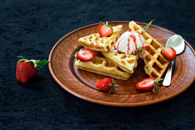 Breakfast. waffles with strawberries, cherries on a plate on a black background