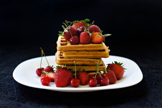 Breakfast. waffles with strawberries, cherries on a white plate on a black background