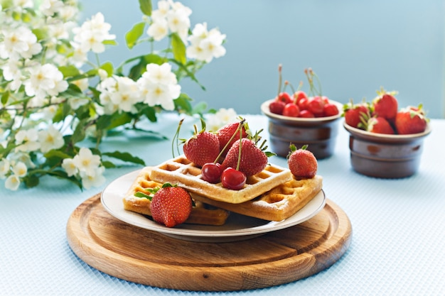 Breakfast. waffles with strawberries and cherries on a wooden board.