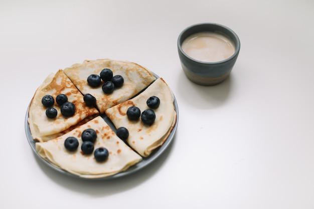 Завтрак с чашкой капучино и блинчиками с черникой на белом фоне, вид сверху