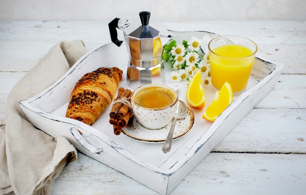 Завтрак с чашкой кофейных круассанов и апельсинового сока.