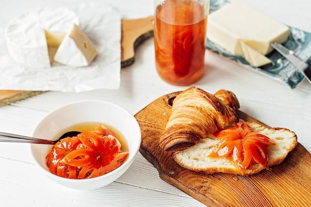 신선한 크루아상과 향기로운 커피 라떼, 귤 잼, 버터, 브리 치즈로 구성된 아침 식사. 과일 조각. 건강한 아침 식사.