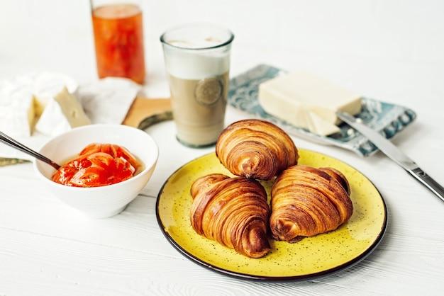 신선한 크루아상과 향기로운 커피 라떼, 귤 잼, 버터, 브리 치즈로 구성된 아침 식사. 건강한 아침 식사.