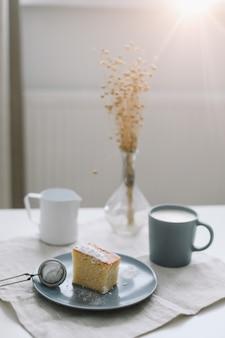 Завтрак с кусочком домашнего торта на тарелке и чашкой кофе