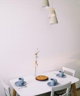 Завтрак с кусочком домашнего пирога и горячим чаем на столе.