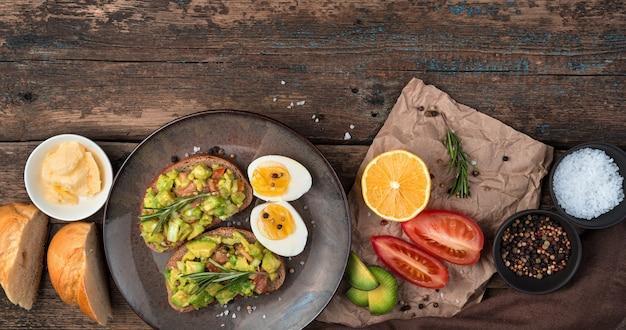 木製の背景にアボカドサンドイッチ、トマト、レモン、バターと朝食。上面図、コピーするスペース、パノラマ。適切な栄養の概念。