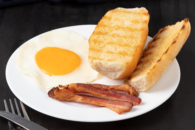 Breakfast with bacon, egg and bread.