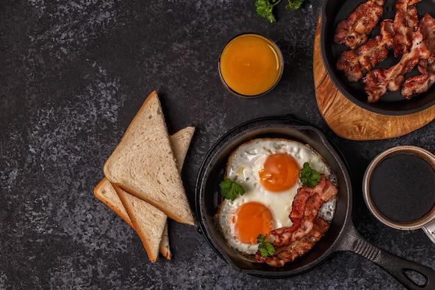 베이컨, 계란 후라이, 커피, 오렌지 주스가 포함 된 조식