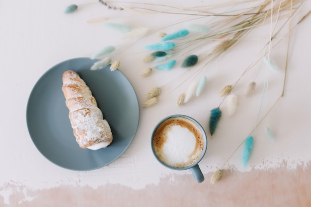 Завтрак с выпечкой и кофе слоеные рулеты со сливками на тарелке и капучино вид сверху
