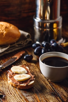 Breakfast with banana sandwich with chocolate spread, coffee cup and grapes