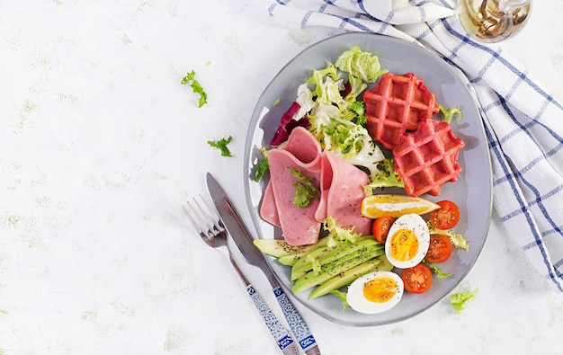 Breakfast with beetroot waffles, boiled egg, ham, tomato and slice avocado on white surface