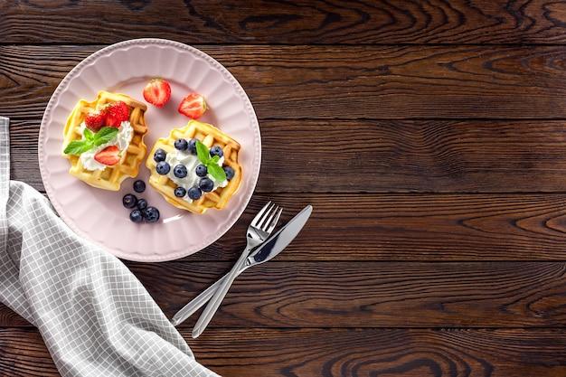 Завтрак с бельгийскими вафлями на темном деревянном