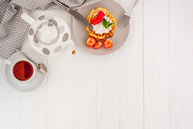 Завтрак с бельгийскими вафлями на белом деревянном